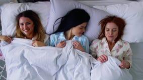 顶视图,三个美丽的女朋友女孩在床上的逗人喜爱的睡衣上床并且投入了睡觉的眼睛绷带 影视素材