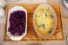 顶视图,土豆泥,在黑碗的烘烤土豆服务用在白色碗的烂醉如泥的紫色圆白菜 库存照片