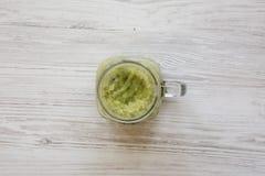 顶视图,在一个玻璃瓶子的绿色芹菜圆滑的人在白色木背景 r 免版税库存图片