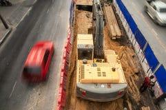 顶视图,在一工地工作的一种被跟踪的挖掘机安全岛的,继续前进柏油路的车 免版税库存图片