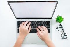 顶视图,妇女的手使用有一个白色屏幕的一手提电脑在一张现代书桌上 r 库存照片