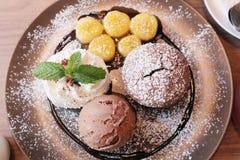 顶视图,巧克力松饼服务与巧克力冰淇凌、打好的奶油和香蕉, ` s冠上用焦糖糖浆 库存图片