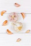 顶视图,平的位置 拨蒜和大蒜电灯泡在一张白色木桌上 库存照片