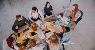 顶视图,愉快的专业商人小组配合在轻的现代办公室,年轻女实业家领导讲话 股票录像
