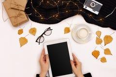 顶视图,片剂计算机特写镜头有黑屏的在妇女的手上在被编织的毛线衣穿戴了 附近杯子  库存图片