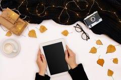 顶视图,片剂计算机特写镜头有黑屏的在妇女的手上在被编织的毛线衣穿戴了 附近杯子  库存照片