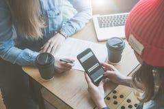 顶视图,特写镜头智能手机在女性手上 两个朋友会议咖啡馆的 女孩学会在网上,喝咖啡 免版税库存照片