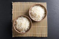 顶视图:在圆的陶瓷碗的蒸的煮熟的印度大米在黑石头 免版税库存照片