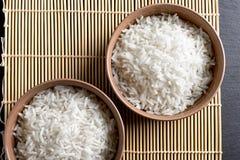 顶视图:在圆的陶瓷碗的蒸的煮熟的白色印度大米在黑石头 免版税库存图片
