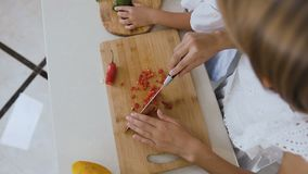 顶视图 一个木板的两个姐妹切了胡椒辣椒和鲕梨烹调的沙拉在厨房用桌上 股票录像