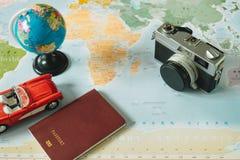 顶视图 减速火箭的照相机、世界、汽车和护照被安置在顶部 免版税库存图片