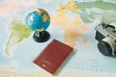 顶视图 减速火箭的照相机、世界和护照被安置在worl顶部 免版税图库摄影