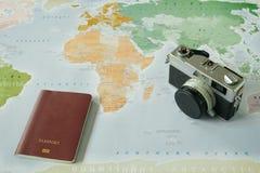 顶视图 减速火箭的照相机和护照安置了在世界地图a顶部 库存照片