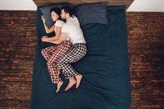 顶视图 在睡衣睡眠的年轻夫妇靠近在床上在家 免版税库存照片