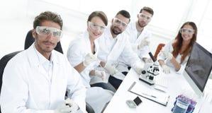 顶视图 坐在工作场所的现代年轻科学家 免版税库存图片