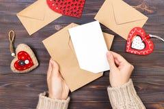 顶视图 女孩文字情书的手在圣徒情人节 与红色心形的图的手工制造明信片 2月14日ho 免版税库存照片