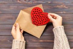 顶视图 女孩文字情书的手在圣徒情人节 与红色心形的图的手工制造明信片 2月14日ho 库存照片