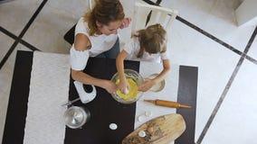 顶视图 帮助她的厨房裂化的鸡蛋的妈妈入碗和混合曲奇饼的小女婴面团 家庭 股票视频