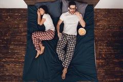 顶视图 年轻人观看的电影和吃玉米花在床上,当妇女附近时睡觉 免版税库存照片