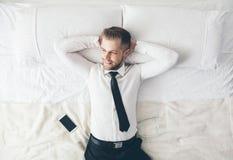 顶视图 放松在床上的英俊的商人在一困难的天以后在工作 库存图片