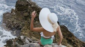 顶视图 站立,海挥动伟大关于他们的近的岩石的帽子的一个女孩 有大帽子的年轻深色的妇女 影视素材