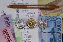 顶视图/花费金钱和付款平的位置说明与硬币、钞票和费用演算用手写 免版税库存照片