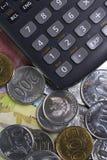 顶视图/花费金钱和付款演算平的位置说明与硬币、钞票和计算器 免版税库存图片