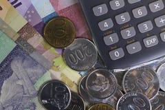 顶视图/花费金钱和付款演算平的位置说明与硬币、钞票和计算器 免版税库存照片