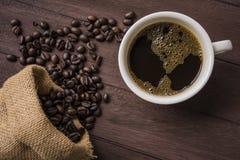 顶视图/Coffee杯子和咖啡豆在木桌上 免版税图库摄影