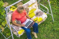 顶视图eldery人开会和放松在使用膝上型计算机的暑假rasort在长沙发的草 免版税图库摄影
