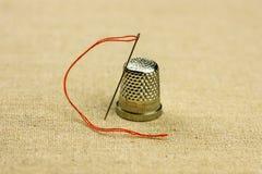 顶针和一支缝纫针与一条螺纹在亚麻制织品,关闭,温暖的自然口气 库存照片