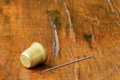 顶针和针在充分一块古色古香的表面饰板镇压 免版税库存图片