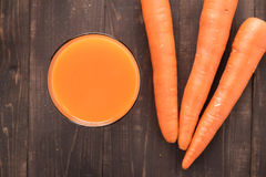 顶面在木背景的射击新鲜的红萝卜汁 免版税库存照片