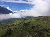 顶面山景天空蔚蓝、云彩、石头和绿叶 库存图片