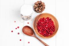 顶面平的看法:在木碗和果酱的蔓越桔与白色表面上的匙子 免版税库存照片