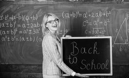 顶面方式欢迎学生回到学校 老师妇女举行回到学校的黑板题字 这是上课时间 免版税库存照片