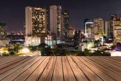 顶面木书桌有都市城市夜视图迷离背景,木桌 库存图片