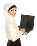 顶头围巾的亚裔年轻回教妇女使用膝上型计算机 库存图片