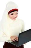 顶头围巾的亚裔年轻回教妇女使用膝上型计算机 免版税库存图片