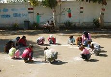 顶头围巾的女老师在学校收集圈子的女孩和画在沙子的 免版税库存照片