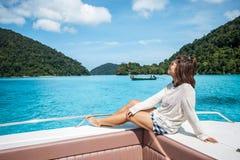 顶头速度小船和看起来的美丽的海美丽的女孩 图库摄影