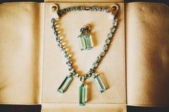 项链和耳环有方形的水晶的在一个皮革小海湾投入了 免版税库存照片