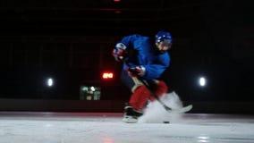 顽童的特写镜头在冰,并且在慢动作曲棍球运动员拔,并且雪飞行入照相机和他 股票视频