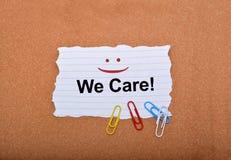 顾客与微笑的关心标志在纸 免版税库存图片