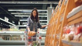 顾客买在面包店部门的面包的可爱的女孩是商店,嗅到它,微笑和投入在购物 股票视频