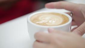 顾客从barista收到一份订单,与拿铁艺术的咖啡的手 股票录像