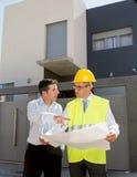 顾客和建设者工头工作者谈话在新房在真实状态企业概念的大厦图纸 库存图片