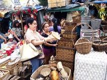 顾客在一家商店在Dapitan市场上检查一个家庭装饰产品 免版税库存图片