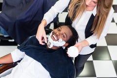 顾客在与剃须膏的理发店 免版税库存照片