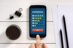顾客在巧妙的电话屏幕上的回顾概念有办公室对象的 图库摄影